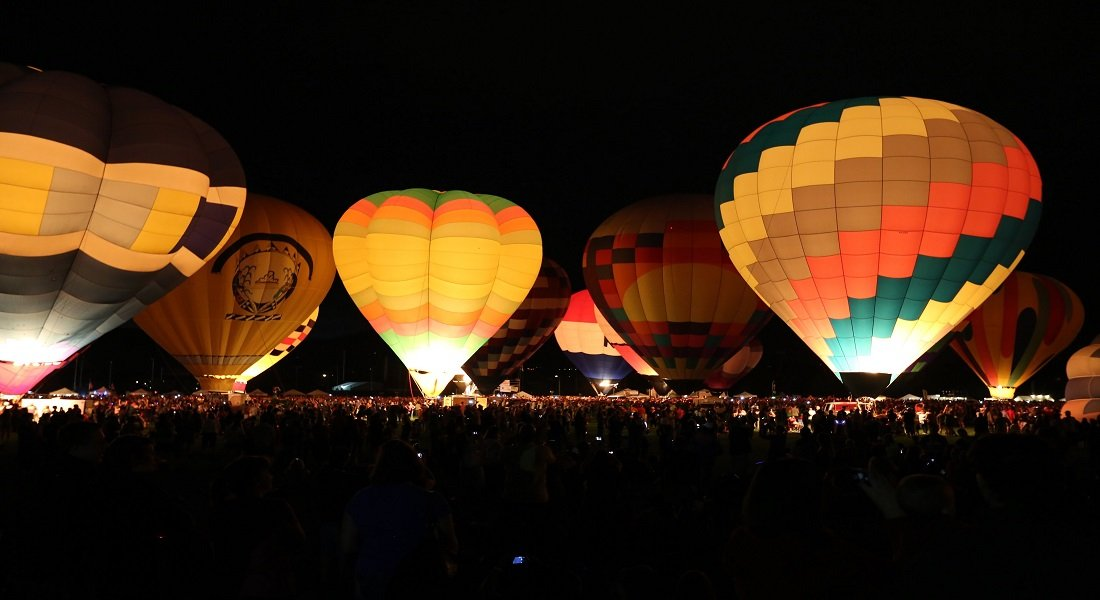 hot air balloons of multi colors lit up in a night sky ready for take off