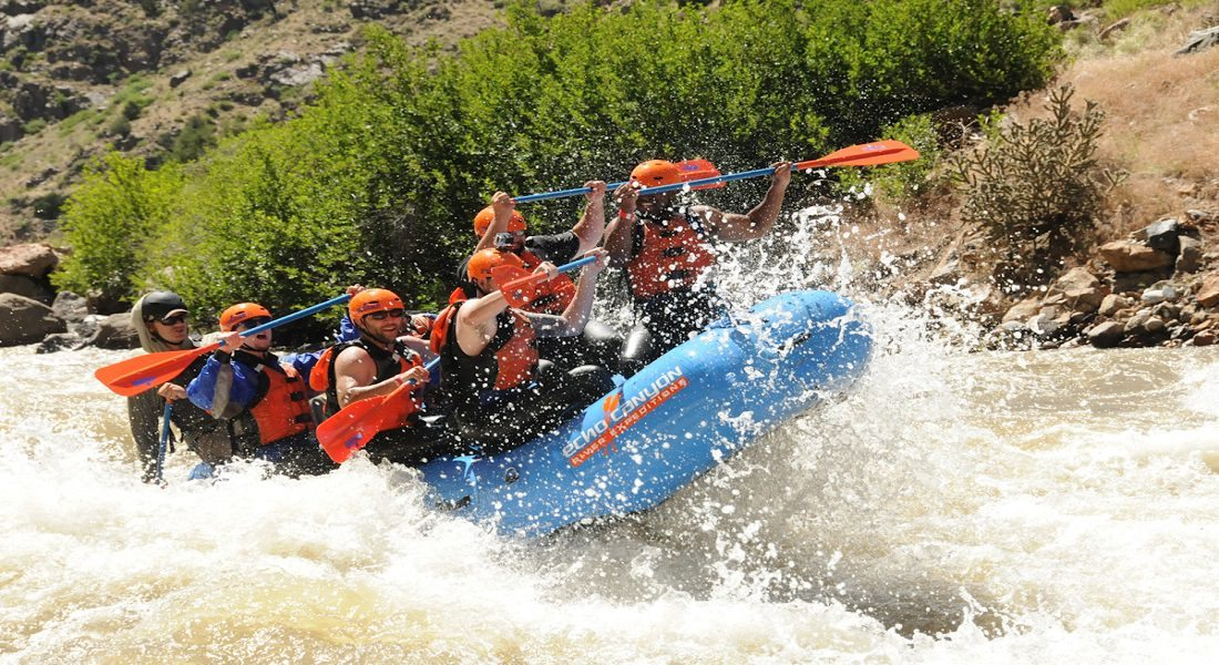 a rafting boat on a river with white rapids with several people in it and the front lifted up like it's about to tip over