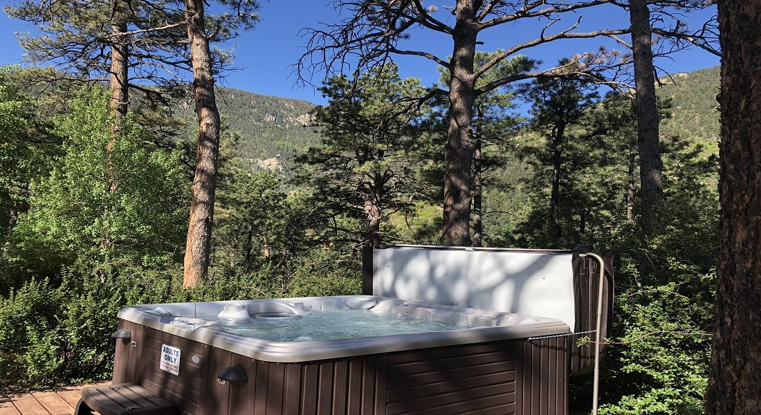 Hot tub in the the trees with mountains in the background with blue skies