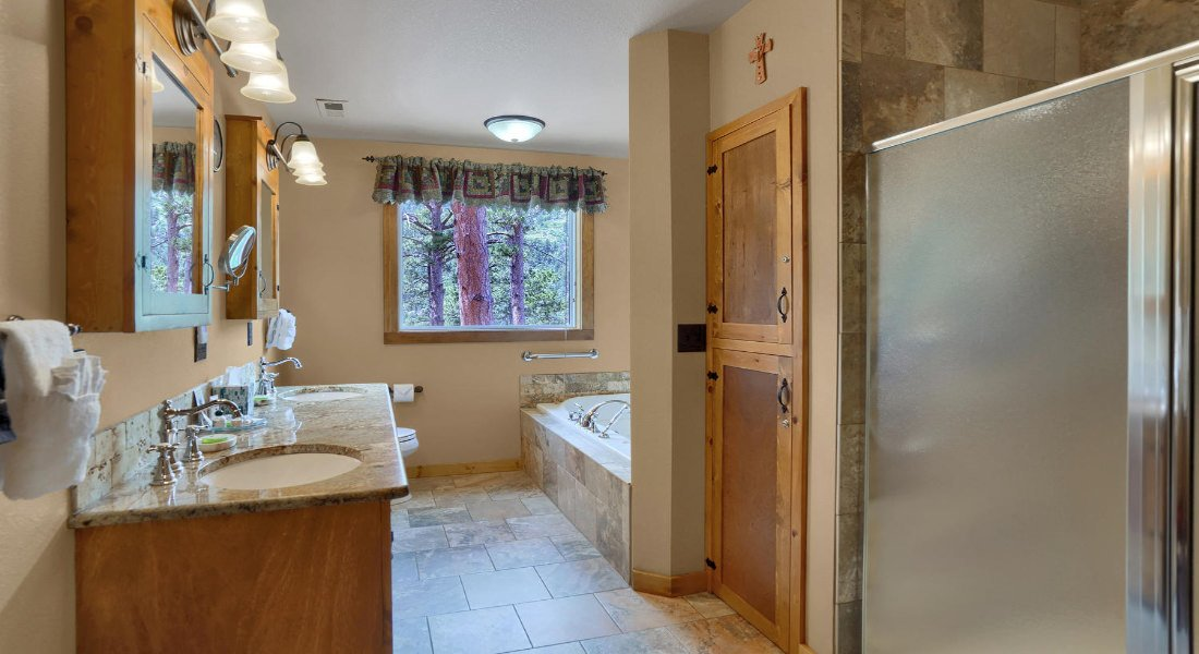 bathroom with sinks, tile floors, large bathtub, shower, and window with trees out the window