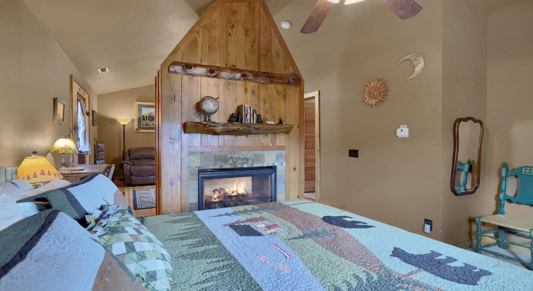 King bed with blue and green quilt with bears and a cabin, and a fireplace with a fire in it.