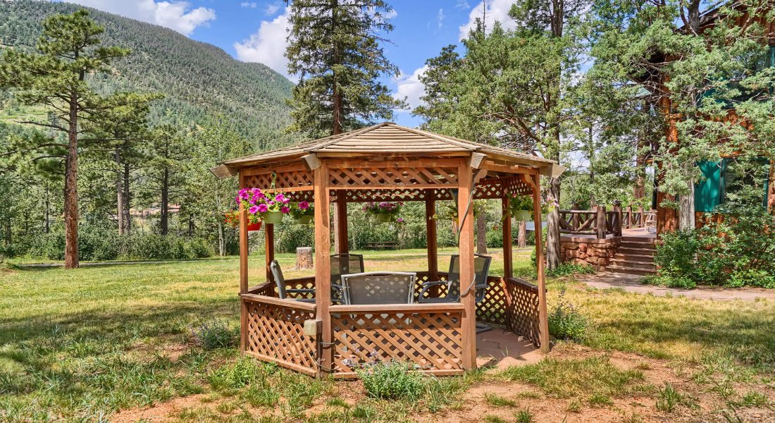 wooden gazebo with flowerpots hanging on the sides, amongst trees and mountains in the background