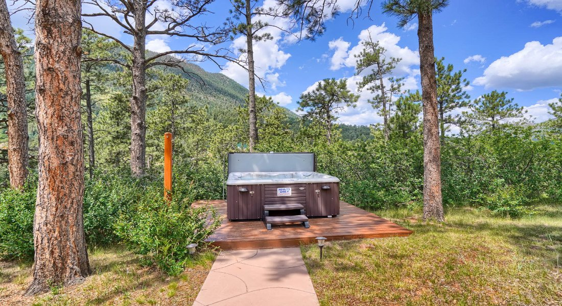 pathway to an outdoor hot tub amongst pine trees, mountains in the back, with blue skies and patches of white clouds