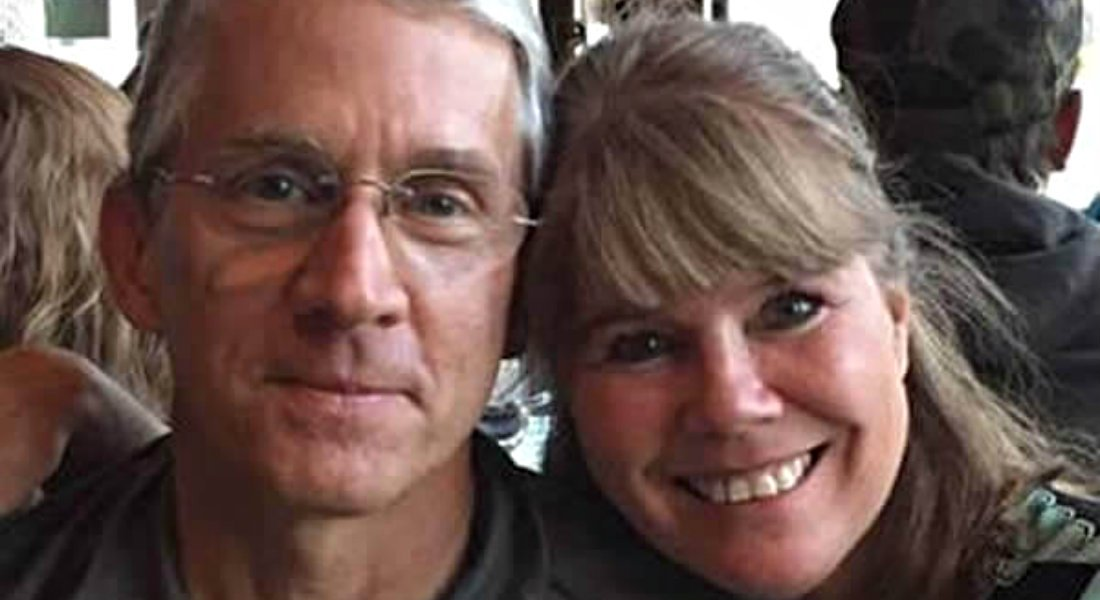Man with gray hair and rimless glasses next to a woman smiling