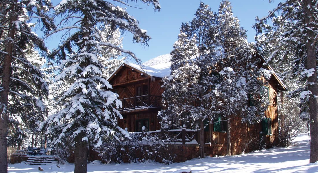 Two story wood cabin with green shutters in a hillside surrounded by snowcapped trees and snow covered ground
