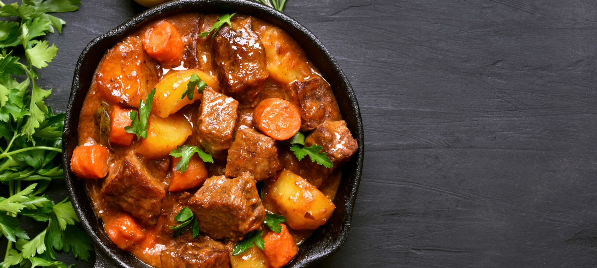 A cast iron pan with beef stew and vetetables