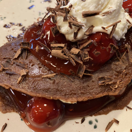 Chocolate crepes with cherry pie filling and cream in between and on top, garnished with shaved chocolate curls