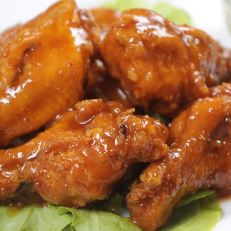 Buffalo Chicken Wings on a bed of lettuce with blue cheese dressing