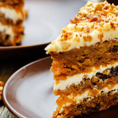 Layeres of Carrot Cake with Cream Cheese Frosting, sprinkled with Chopped Nuts