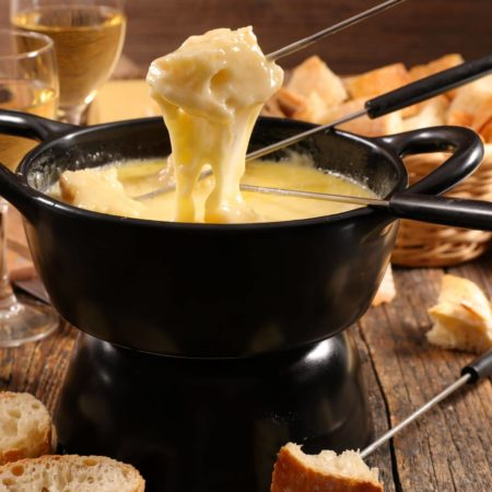 Black fondue pot with melted cheese and dipped bread with wine and more bread and cheese in the background