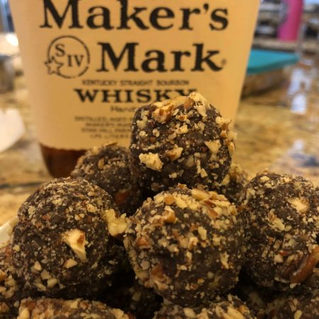 Round dark brown dough balls coated with chopped pecans and a bottle of bourbon whiskey in the background