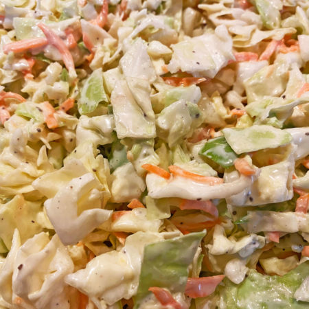 Cabbage salad with green cabbage, orange carrots, and spices in a white creamy sauce
