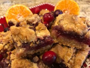 Square bar cookies with golden crumble crust and red filling adorned with cranberries and oranges