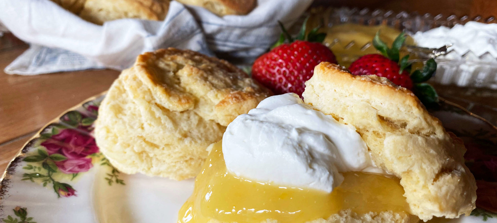 Flaky golden scones with lemon curdc devonshire cream, and fresh strawberries