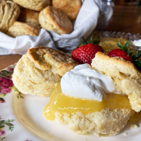 Flaky golden scones with lemon curdc devonshire cream, and fresh strawberries