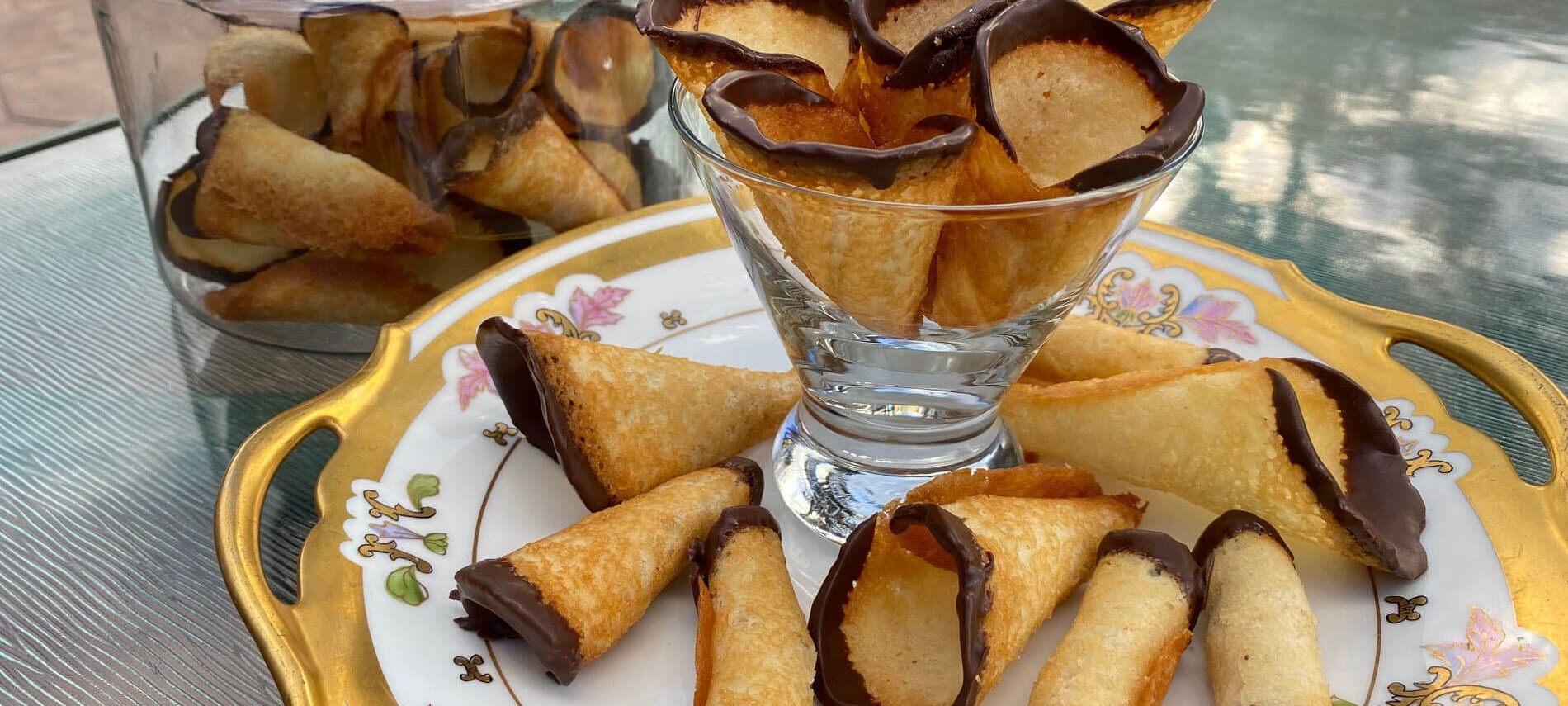 Cone shaped golden cookies in a martini glass and on a plate with the edges dipped in chocolate
