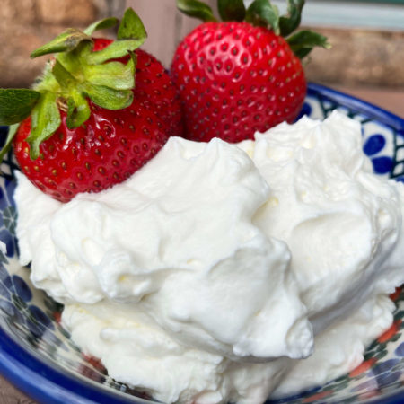 Light and Fluffy Cream with fresh red strawberries with green leaves