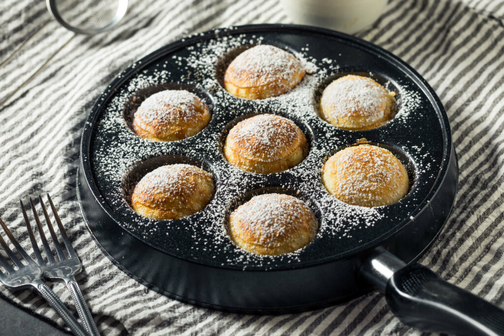 Ebelskiver Pan with round pancakes dusted with powdered suger
