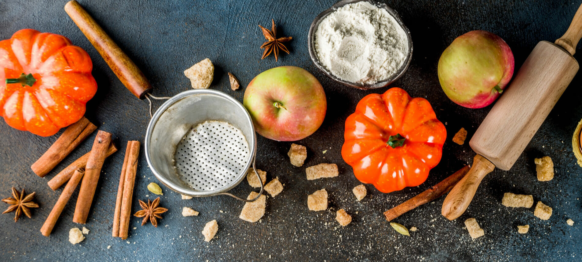 Fall Baking ingredients of apples, pumpkins, flour, and spices