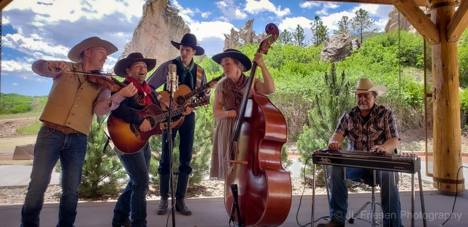 Flying W Wranglers playing western instruments and singing in front of red rock formations