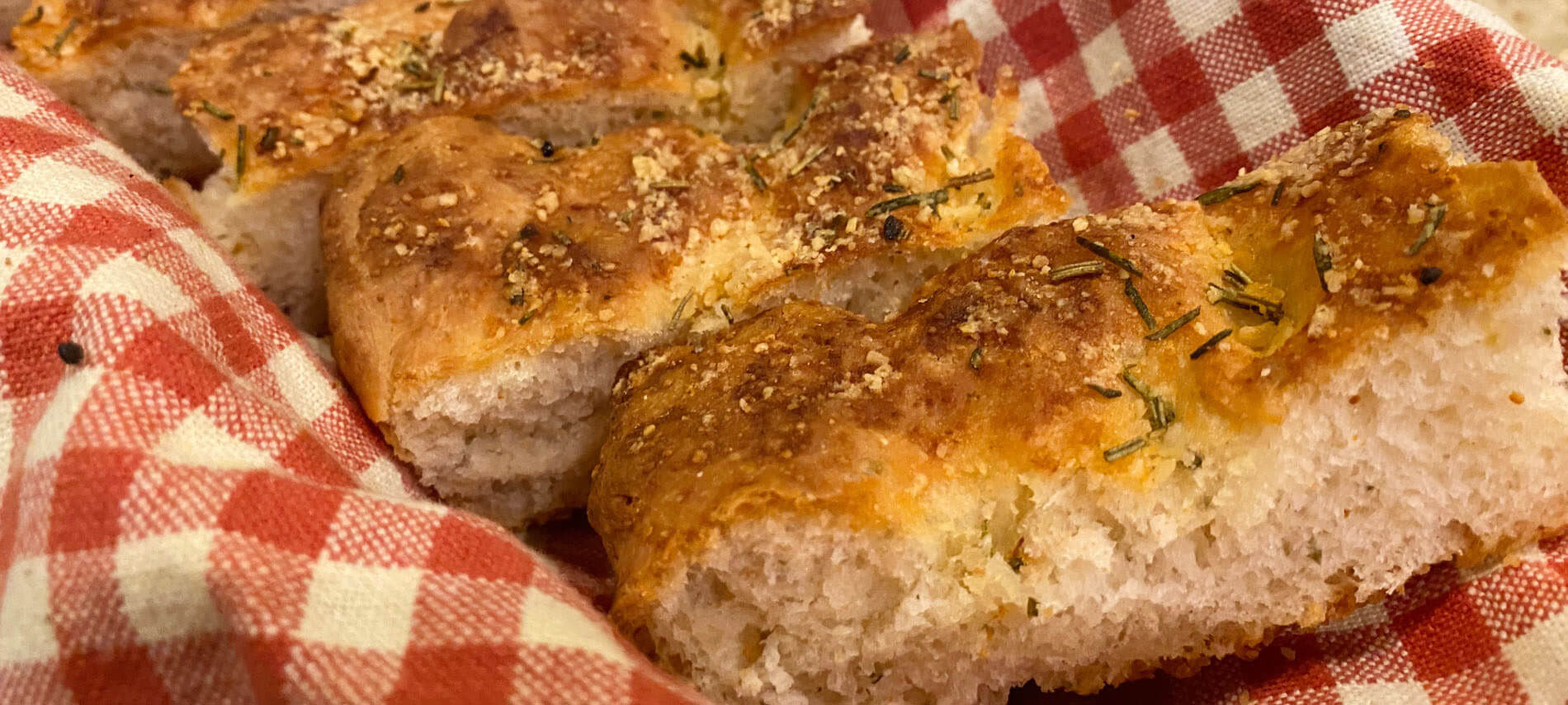 Slices of focaccia bread with rosemary and sea salt on a red and white checkered cloth