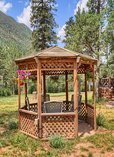 Wood lattice gazebo with chairs inside and hanging pots of pink flowers, amogst trees, mountains and blue skies in the background