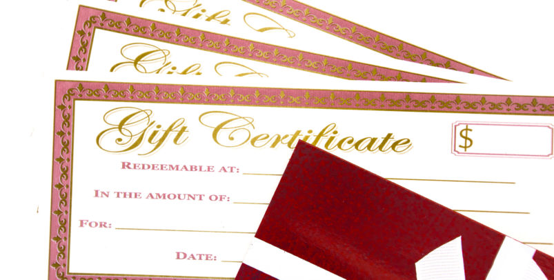 3 rectangular gift certificates with a fancy border and gold writing with a red gift box and white ribbon