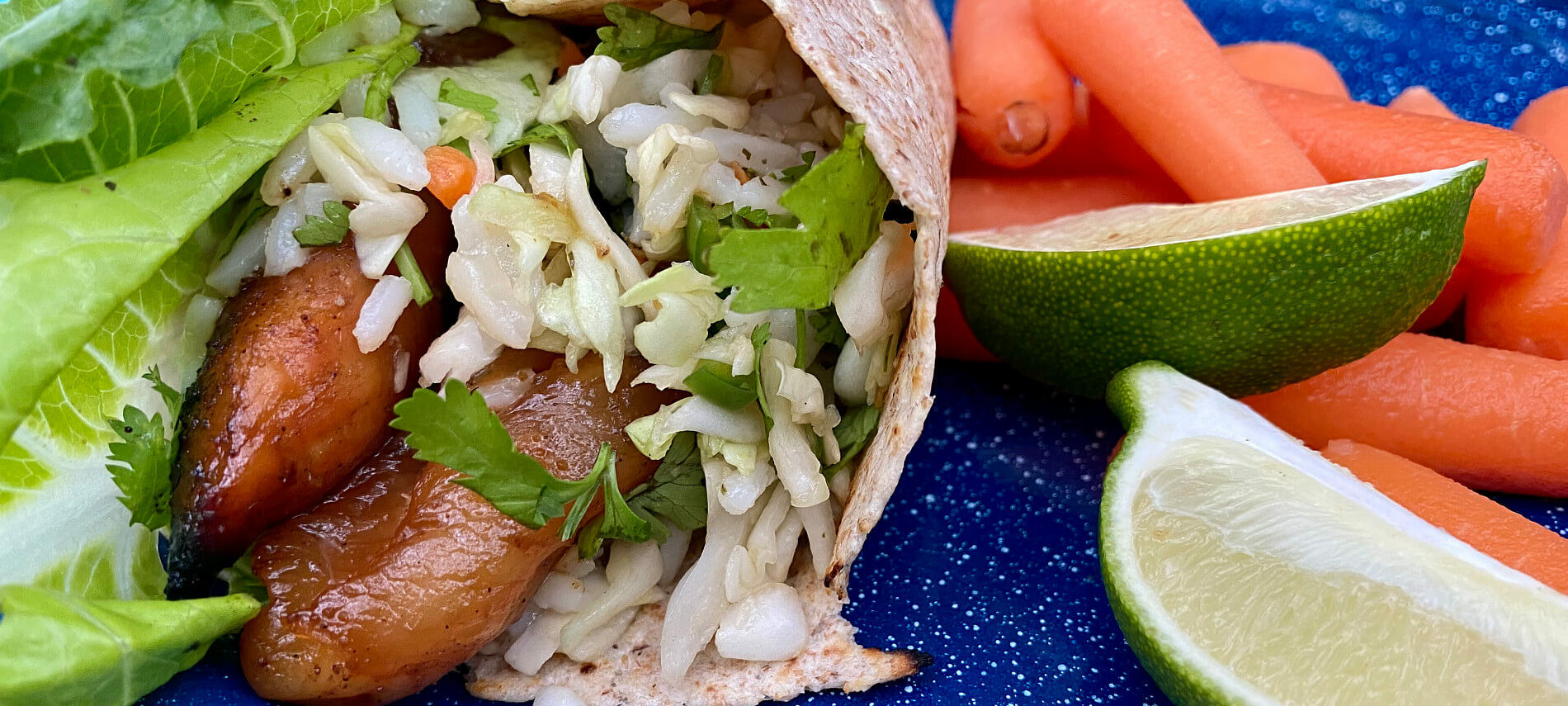 Ginger Chicken Wraps on a blue plate with carrots and limes