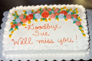 Rectangular cake with white frosting, purple, orange and pink flowers, green leaves, and orange writing