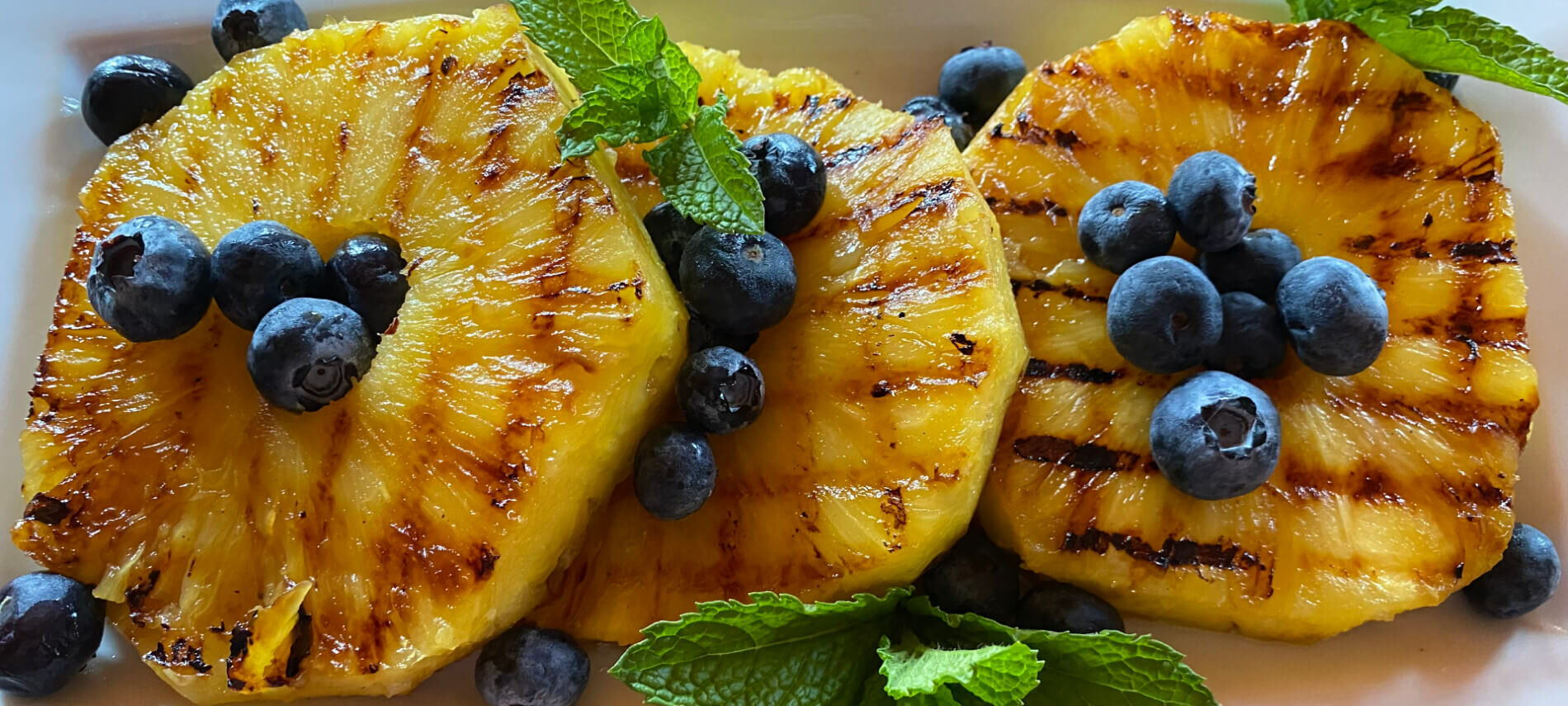 Grilled Pineapple Slices with blueberries and mint leaves on a white plate