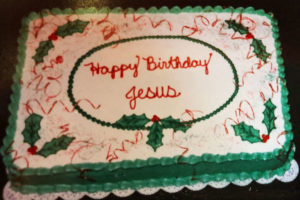 Rectangular cake with white frosting, decorated with green holly leaves and red holly berries, red ribbon, with Happy Birthday Jesus in the middle