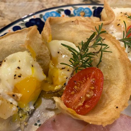 Fluted Crepes filled with a poached egg and runny yolk and cheese with herbs and a sliced tomato