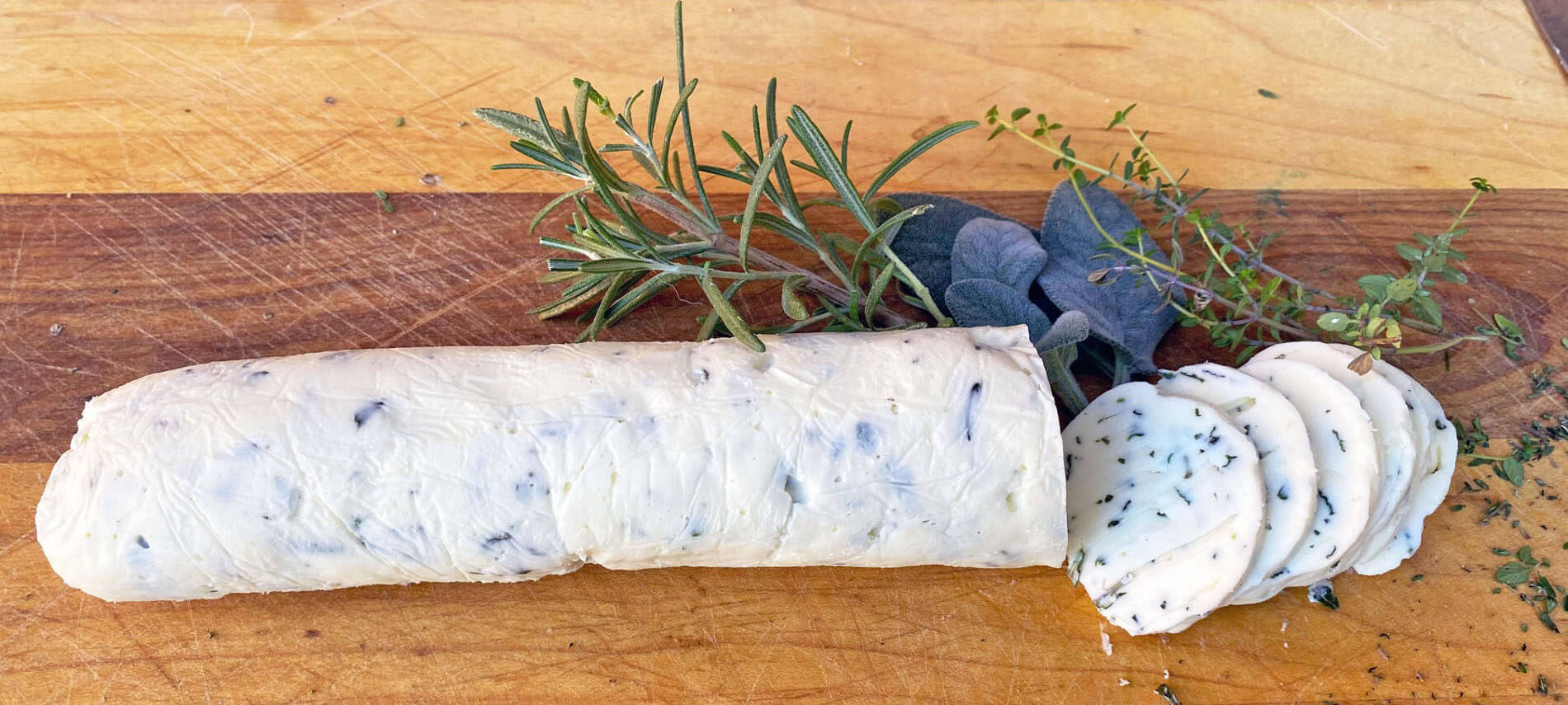 Log of white butter with flecks of herbs in the butter with fresh rosemary, sage leaves, and thyme