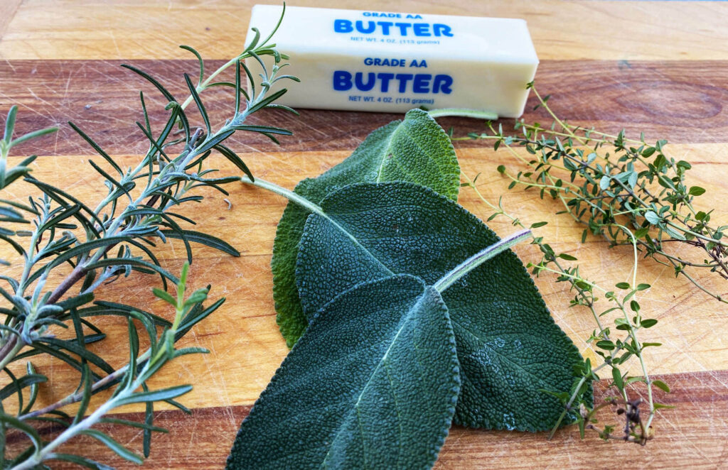 Butter, Rosemary, Sage and Thyme on a wooden cutting board
