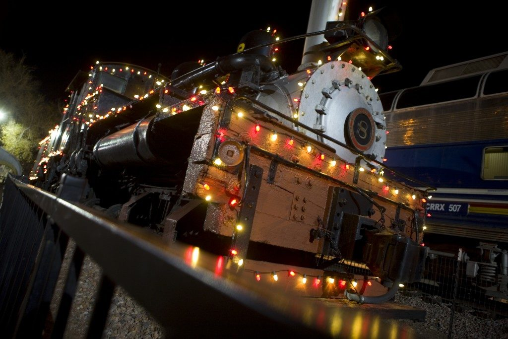 Front of train at night decorated with Christmas lights
