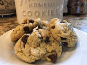 Buttery cookies with chocolate chips and a cookie jar in the background