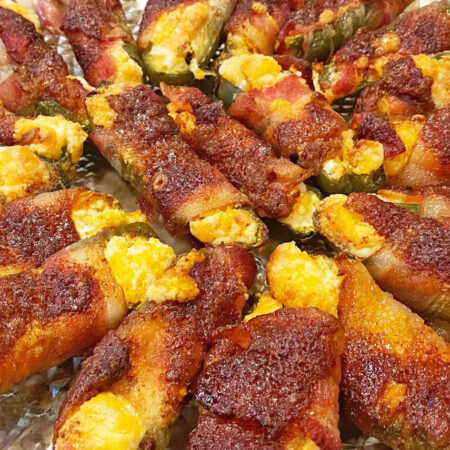 Bacon Wrapped Jalapeno Peppers filled with cheese and sprinkled with brown sugar and chili powder