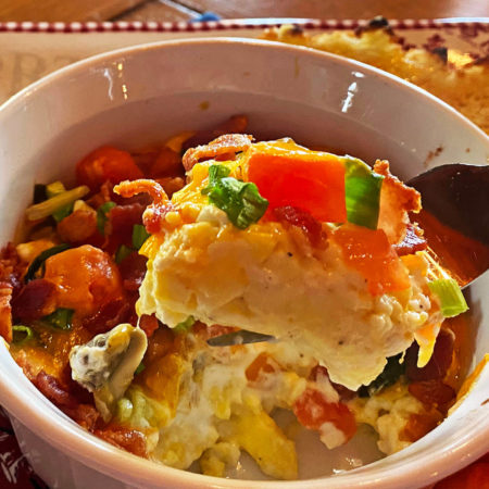 baked eggs in a white dish with tomatoes, onions, bacon and cheese