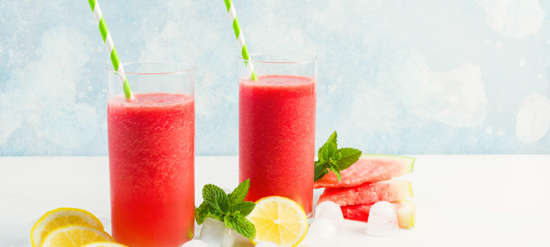 Glasses of red watermelon and lemon slush with lemons, watermelon and lemons, with green and white striped straws