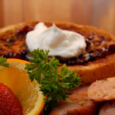Golden thick French Toast with a a purple Lingonerry topping, whipped cream, sausage, and garnished with fruit and parsley