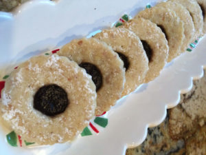 Round nutty cookies with cut out in the middle filled with a reddish purple jam, sprinkled with powdered sugar