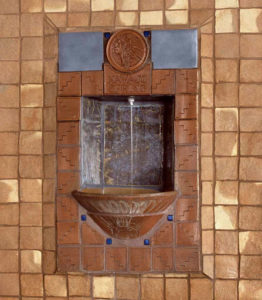 Fountain with running water with brown tiles around.