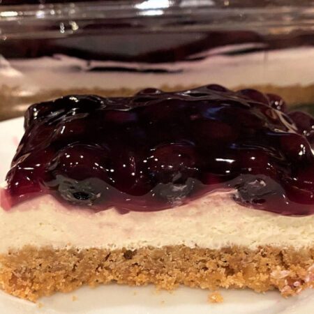 Blueberry Cheesecake with a graham cracker crust, cream cheese filling, and blueberry topping