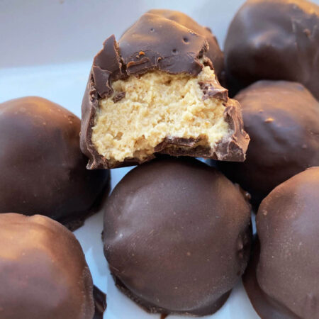 creamy peanut butter balls dipped in dark chocolate on a white plate