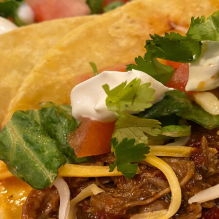 pork tacos with lettuce, tomatoes, shredded cheese and sour cream