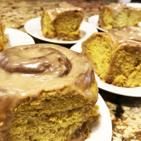 Deep yellow pumpkin cinnamon rolls with brown spicy icing