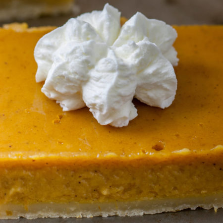Square orange pumpkin bars with a crust and a dollop of whipped cream