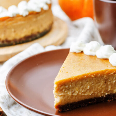 Orange pumpkin cheesecake with a brown gingerbread crust and dolloped with whipped cream on and brown plate and pumpkins as decorations