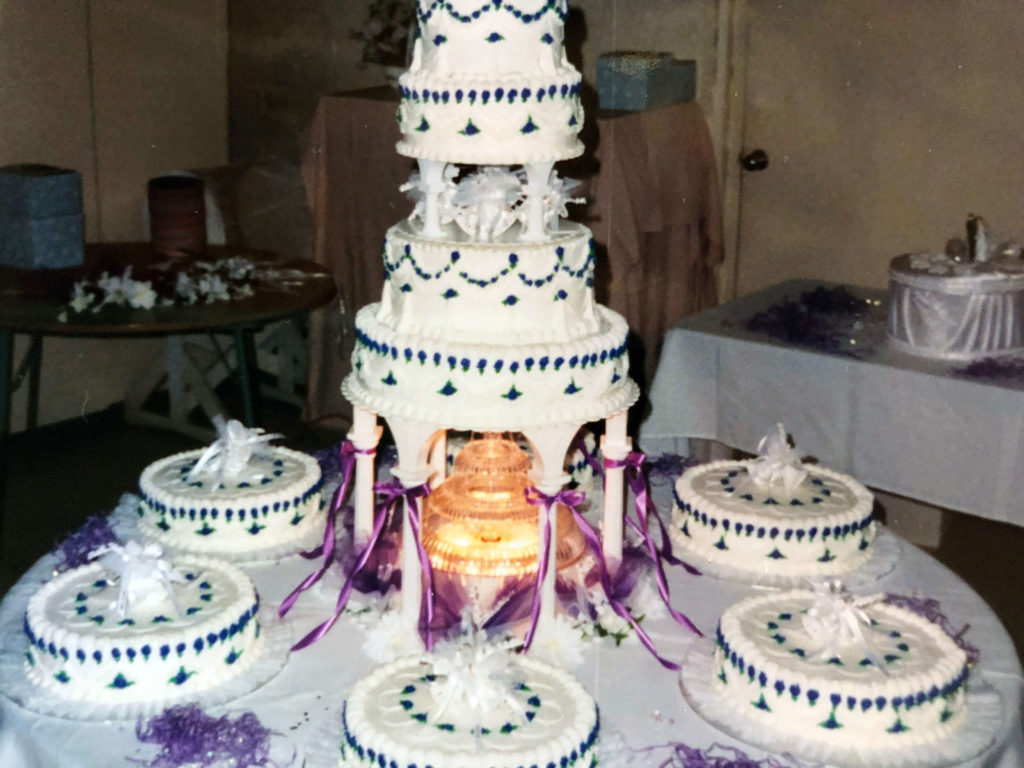 Multi layer cake with fountain underneath and several cakes around it, decorated n purple and white frosting