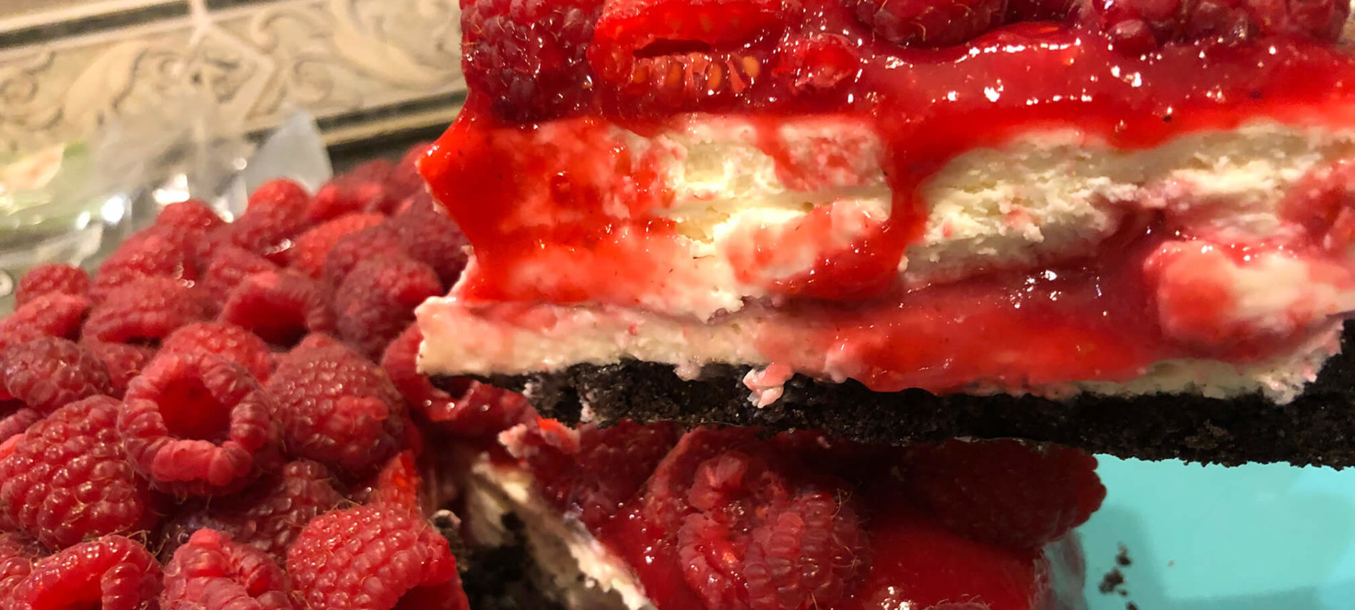 Creamy White Cheesecake with a red raspberry sauce topped with fresh strawberries, under a dark brown chocolate crust